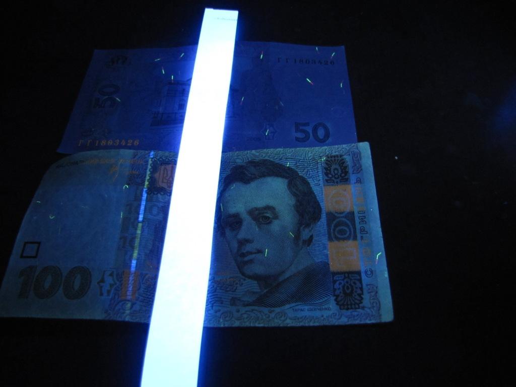 Бумага и денежные купюры в ультрафиолетовом свете