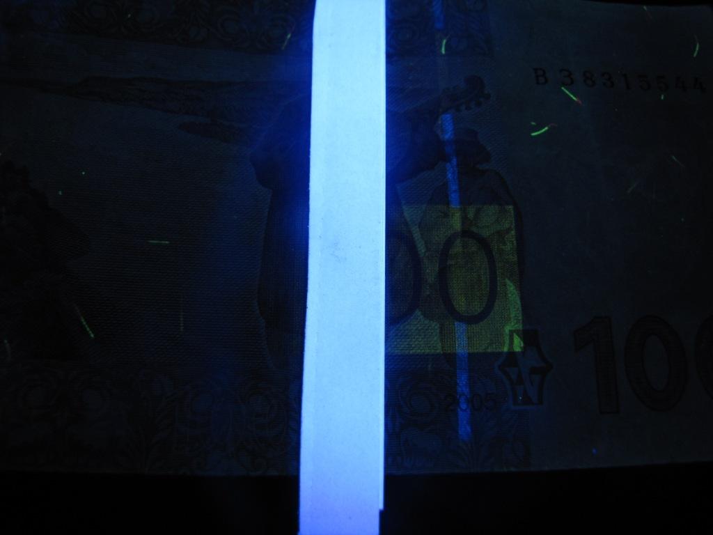 Купюра 100 гривен и принтерная бумага в ультрафиолетовом свете