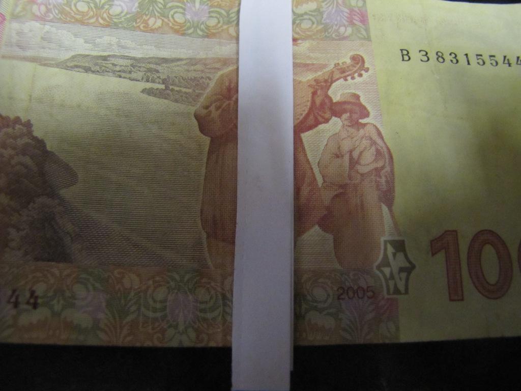 Купюра 100 гривен и принтерная бумага при электрическом свете