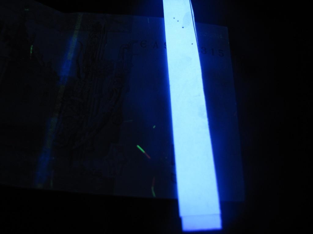 Купюра 5 гривен и принтерная бумага в ультрафиолетовом свете
