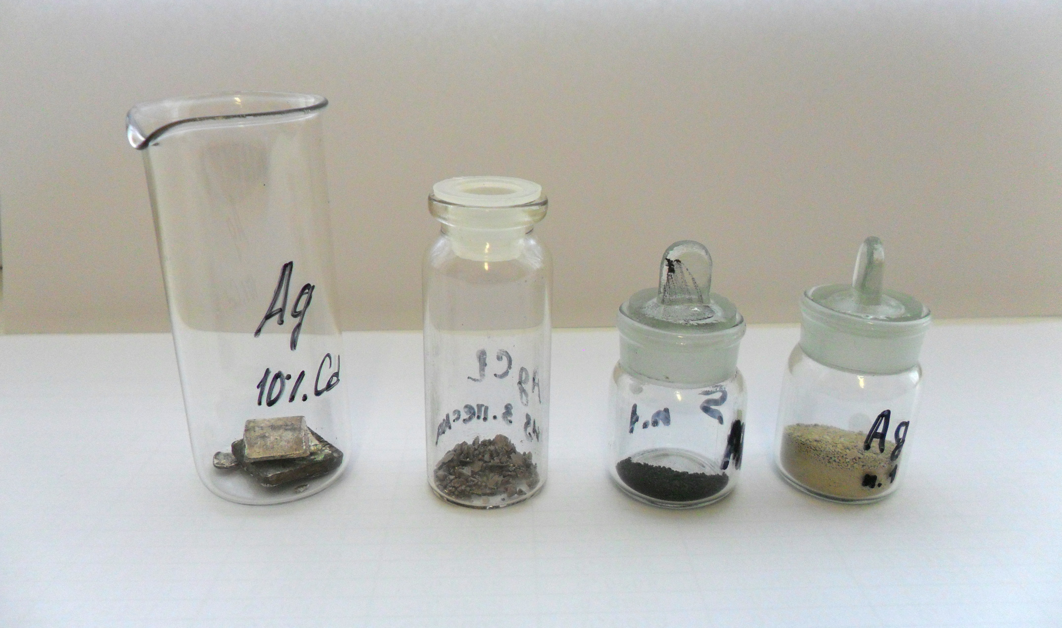 Серебро и его соединения. Слева направо: серебряные контакты реле (сплав, содержащий 10% кадмия); кристаллы хлорида серебра, выросшие из аммиачного раствора (металлический блеск из-за восстановленного на поверхности под действием света серебра); сульфид серебра; серебро, восстановленное из хлорида цинком