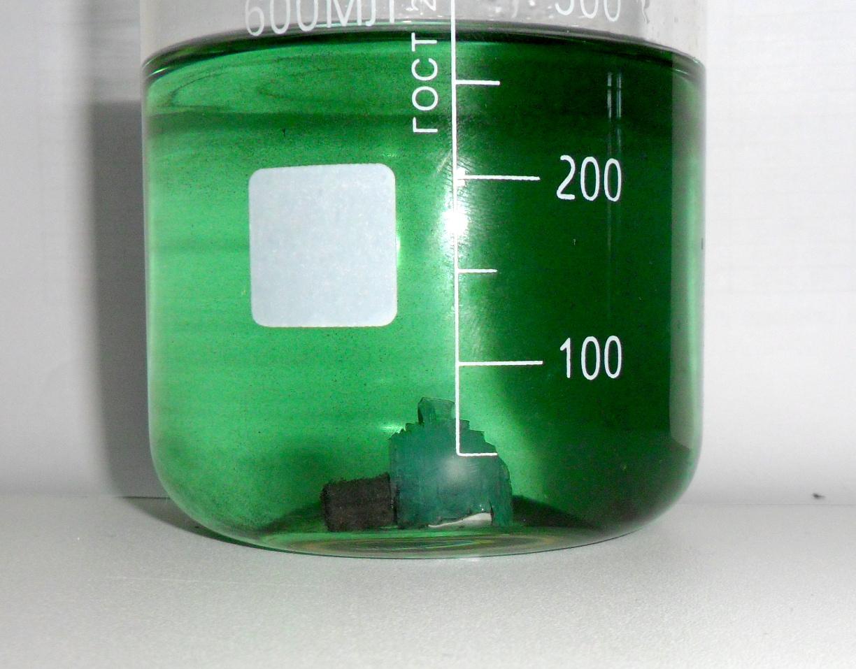 Кристалл сульфата железа (II), выросший за ночь на железном стержне, помещенном в раствор железного купороса для восстановления железа (III) в железо (II). Черная взвесь - частички сульфида железа.