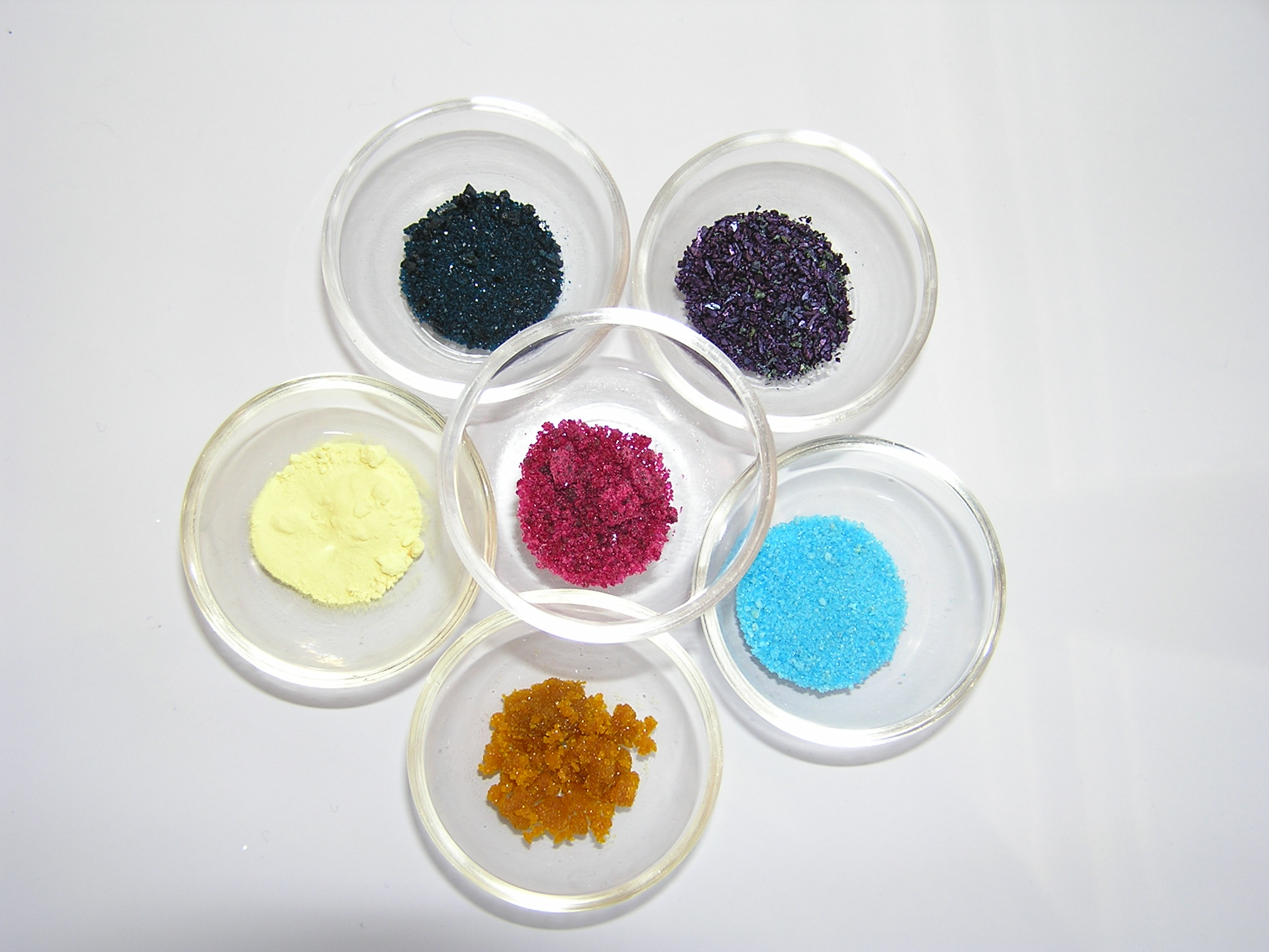 С левого нижнего угла по часовой стрелке: сера, ацетат меди, перманганат калия, сульфат меди, хлорид железа (III), хлорид кобальта (в центре)