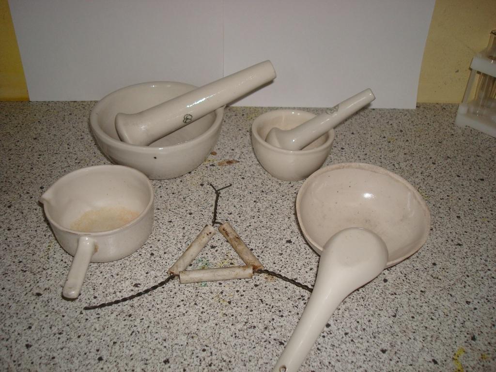 Фарфоровая посуда. Сзади ступки с пестами, в центре - фарфоровый треугольник для тиглей, справа выпарная чашка и фарфоровая ложка