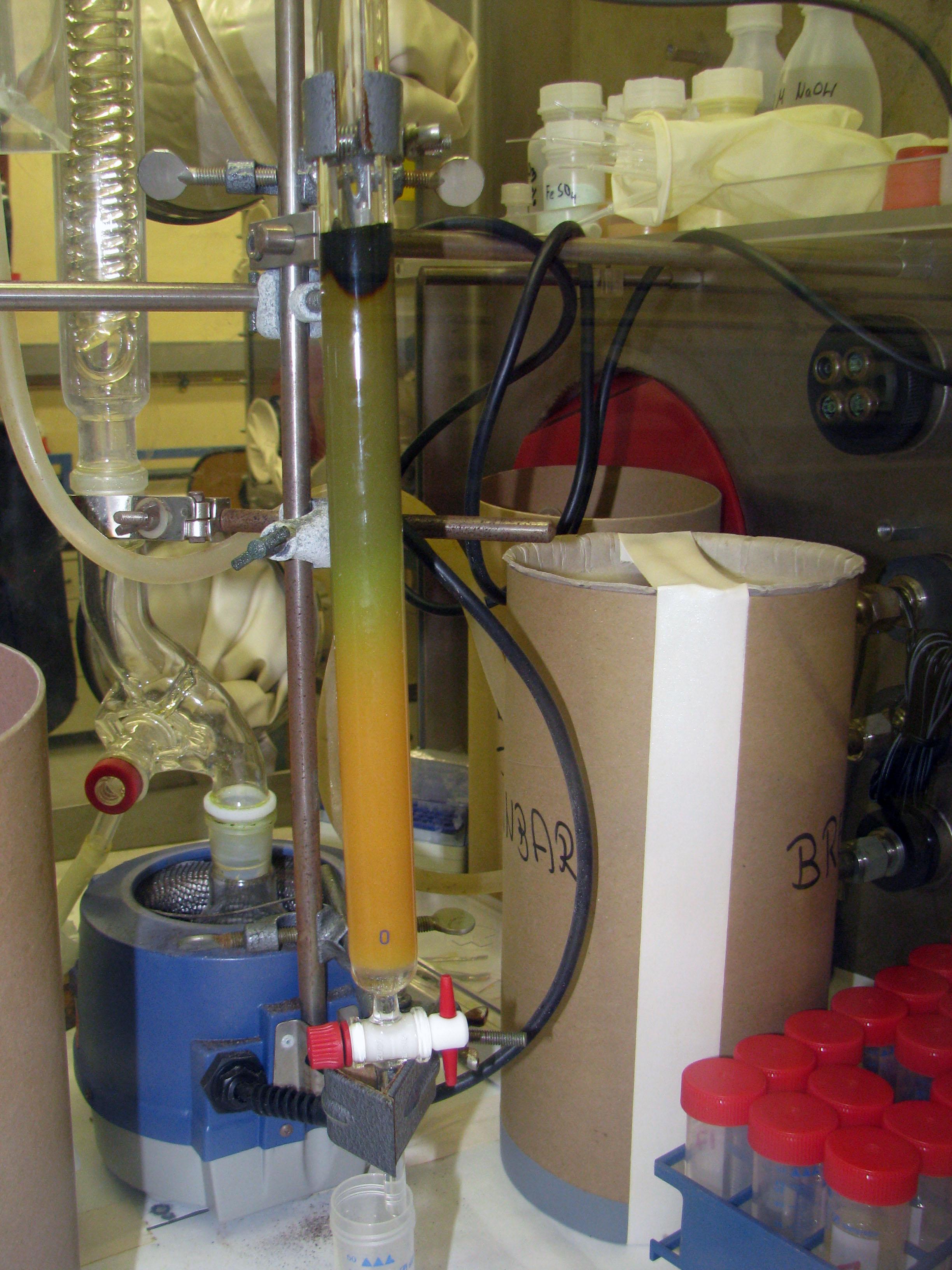 Процесс  начинается.  В  среде  концентрированной  соляной  кислоты Np(IV) образует  анионные  комплексы,  вследствие  чего  нептуний  задерживается  на колонке. На фотографиях  виден фронт  распространения  нептуния.  К  сожалению, частично  через  колонку  проходил  иод,  который  впоследствии  несколько  мешал. При повторной очистке этого удалось избежать удалением кристаллического йода с верха колонки (на фотографиях виден иод наверху).