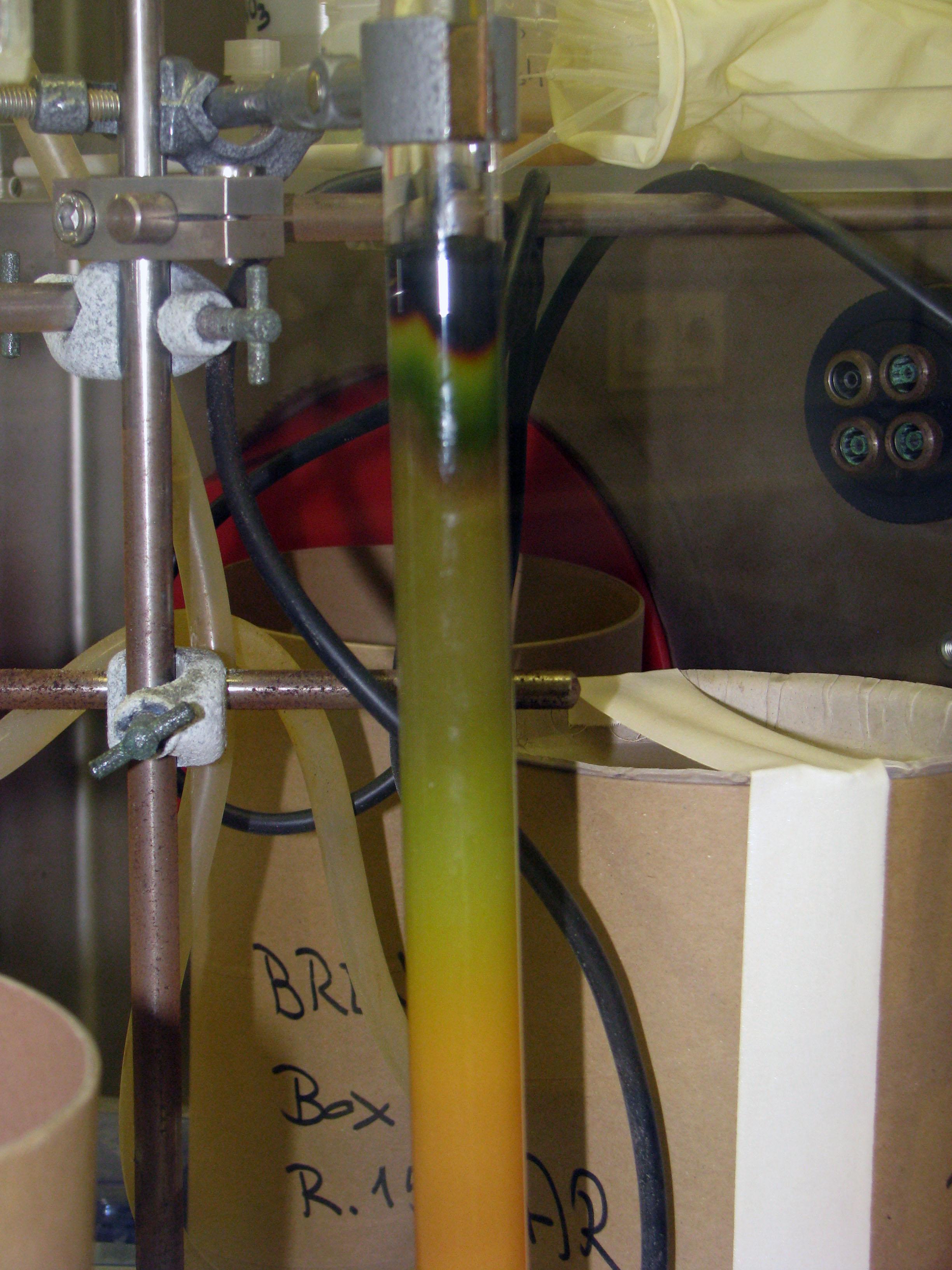 Процесс пошел. При промывании 2 М соляной кислотой анионные комплексы Np(IV)  разрушаются  и  нептуний  начинает  элюироваться.  На  фотографиях  четко виден фронт продвижения нептуния (зеленый цвет). На последней фотографии видно начало элюирования смеси нептуния и иода.