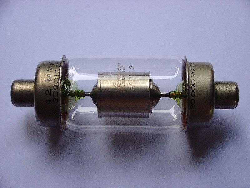 20-киловольтный вакуумный конденсатор (Jennings VC12) на 12-пикофарад с фрагментами из светло-зеленого уранового стекла. Этот 200-граммовый конденсатор имеет длину около 16.5 см и диаметр 6 см. 12-picofarad, 20-kilovolt vacuum capacitor (Jennings VC12) with pale green uranium glass lead-in seals. This 200-gram capacitor is about 16.5 cm long and 6 cm in diameter.