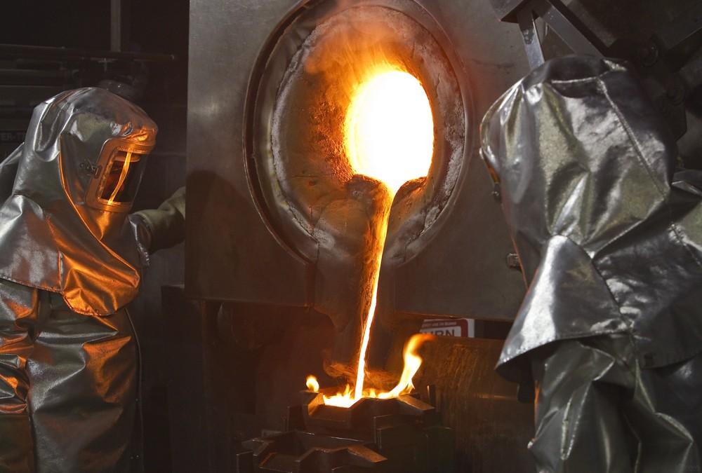 Рабочие в защитных костюмах выливают расплавленное золото в формы