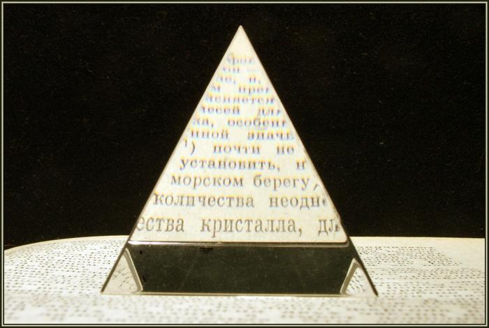 Стеклянная пирамидка на книжном листе