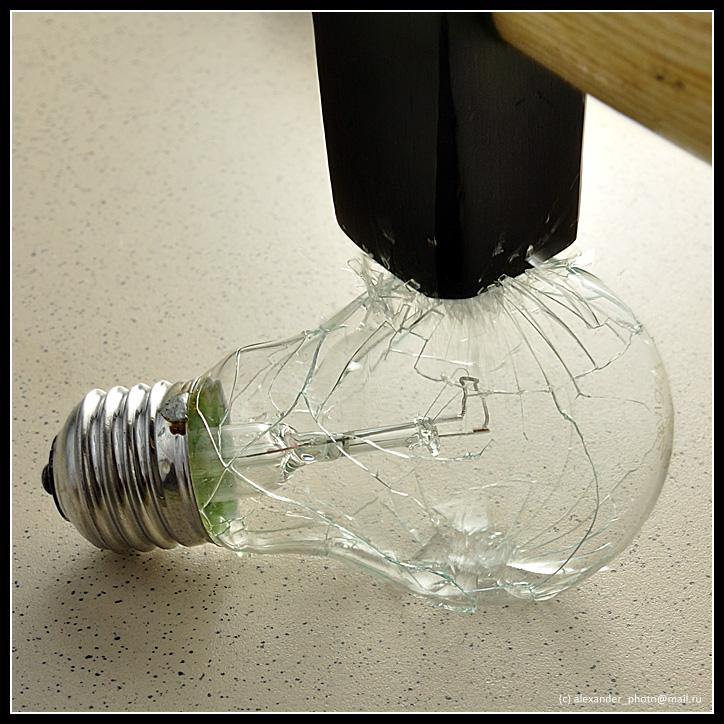 Фотография момента удара молотка по колбе лампочки накаливания