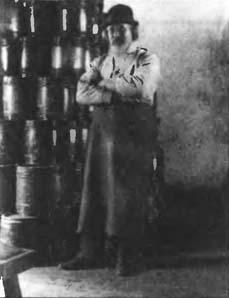 Рабочий фабрики Дюпонов рядом с бочонками c порохом