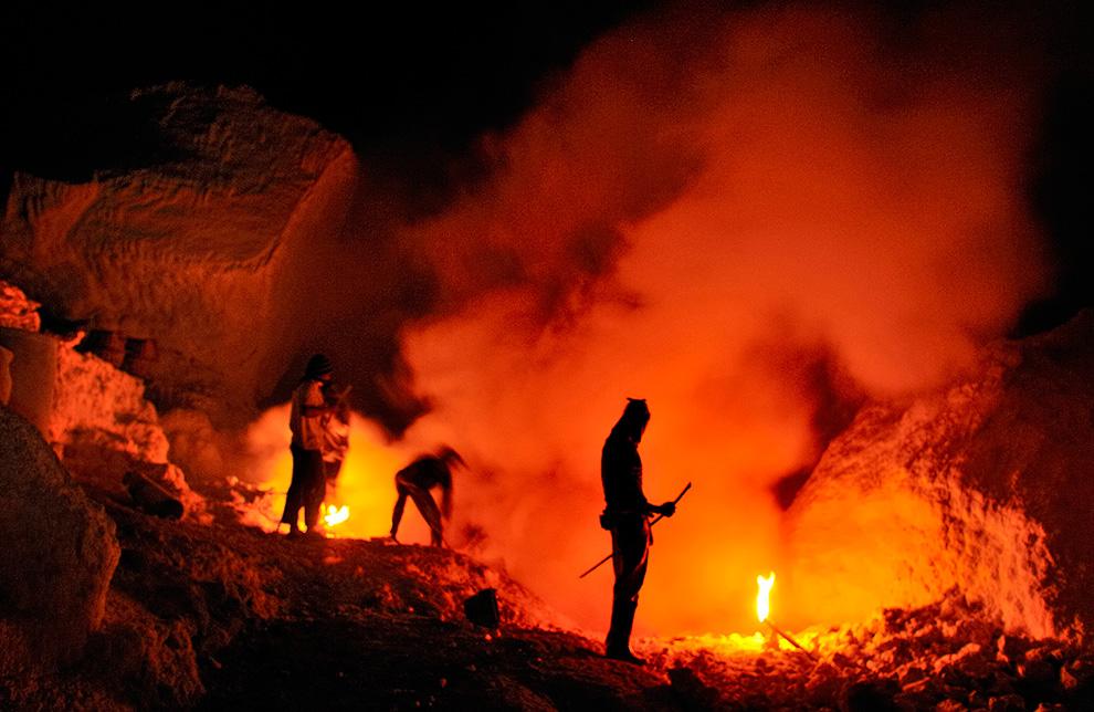 Шахтеры вырубают глыбы из освещаемых факелами залежей серы, затем дробят ее на куски, которые смогут унести.