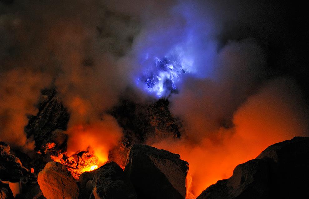 Шахтер добывает серу, работая вблизи конденсационных труб. На заднем плане видно горящую расплавленную серу.