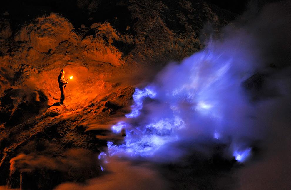 Шахтер стоит ночью в кратере Кава Иджен, держит факел и смотрит на поток жидкой серы, горящей синим пламенем.