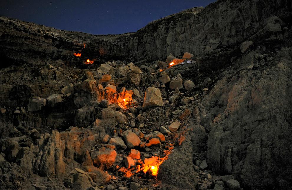 Шахтеры с факелами взбираются по стене кратера Кава Иджен. Они возвращаются по 200-метровому подъему к кайме кратера.