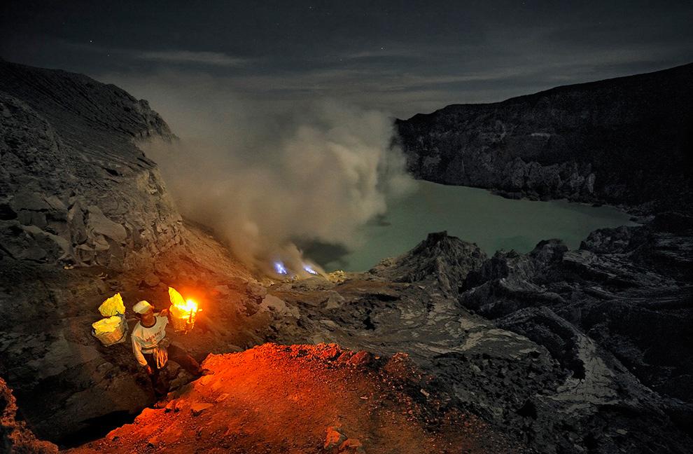 Вид сверху на добычу ископаемых в вулкане: горящая сера, кислотное озеро и залитые лунным светом стены кратера.