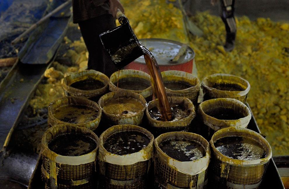Переливание расплавленной серы из плавильной емкости в ведра для переноски.