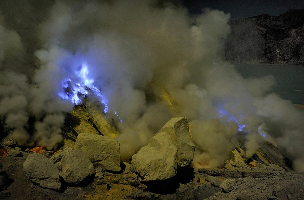 Кислотные вулканические газы выделяются из отверстий среди желтых кусков серы и горящей жидкой серы на Кава Иджен.