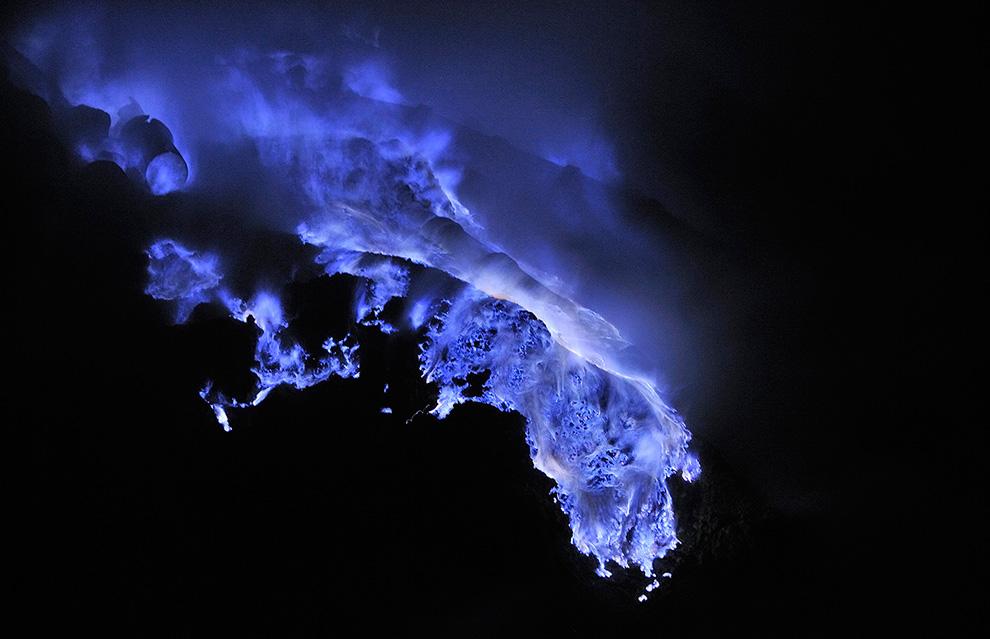 Горящая расплавленная сера течет по кратеру вулкана. Температура плавления серы 115°C. Температура в кратере недостаточно высока для самовоспламенения - огонь загорелся от факела рабочего.