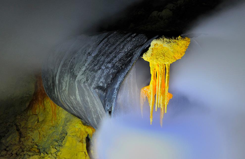 Сера висит на краю старой бочки, которая замурована в залежах внутри Кава Иджен.