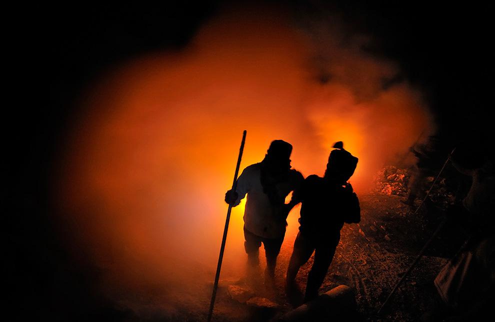 Шахтеры отдыхают возле огня, держа длинные ломы. Они используют их для добычи серы в кратере.